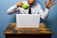 Unbeholfener Geschäftsmann, der Kaffee auf seiner Laptop-Computer verschüttet Lizenzfreie Stockfotos