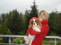 Unbekümmerter König Charles Spaniel Dressed im Regenmantel, in den Armen der Frau Lizenzfreie Stockfotos