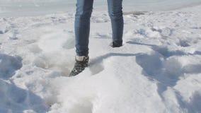 Unbekannte Frau in den Jeans und im Trekkingswinter beschuht das Gehen in tiefen Schnee stock video
