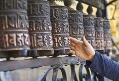 Unbekannte Person, die buddhistische Gebetsräder spinnt lizenzfreie stockfotos