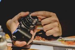 Unbekannte Person, die eine Kamera mit einer Weinleselinse hält stockfotos