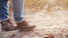Unbekannte Person, die entlang die staubige Straße geht Nahes hohes des Fußes stock footage