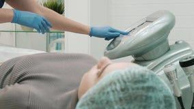 Unbekannter Frauen-Meister eines Cosmetology-Raumes justiert das Ger?t stock video footage