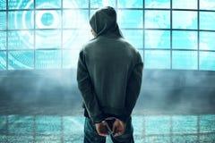 Unbekannter Hacker in den Handschellen im Monitorraum Lizenzfreie Stockfotos
