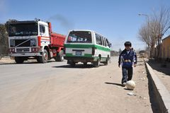 Unbekannter Junge, der mit einem Ball auf der Straße von Oruro spielt Lizenzfreie Stockbilder