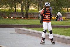 Unbekannter Junge zieht auf Rollen entlang dem Boulevard von Pushkin in D um Lizenzfreie Stockfotos