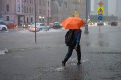 Unbekannter Mann, der auf eine überschwemmte Straße geht
