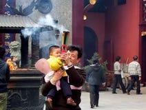 Unbekannter Mann mit einem Kind, das Räucherstäbchen am Stadt-Gott-Tempel hält Stockfotografie