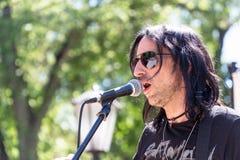 Unbekannter Sänger singt in das Mikrofon im Park stockfotos