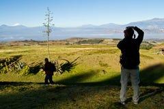Unbekannter Tourist, der ein Foto von Cotopaxi-Vulkan macht Lizenzfreie Stockbilder