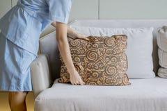 Unbekanntes Mädchen, das Kissen auf der Couch ordnet stockfotografie