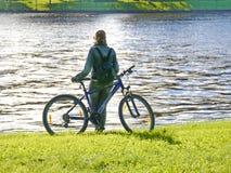 Unbekanntes Mädchen mit Fahrrad am Flussufer Stockfoto