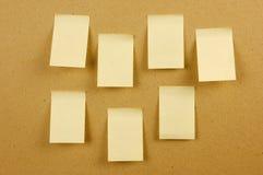 Unbelegte Blätter Papier hielten an dem Wandbraun fest Stockfotos