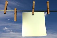 Unbelegtes Blatt Papier hängend an einem Seil Lizenzfreies Stockbild