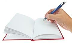 Unbelegtes Buch mit Feder und der Hand stockfotografie