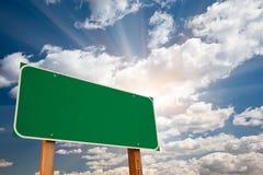 Unbelegtes grünes Verkehrsschild vorbei Wolken und Sonnendurchbruch lizenzfreie stockfotografie