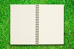 Unbelegtes Notizbuch geöffnet auf Feld des grünen Grases Stockfotografie
