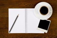 Unbelegtes Notizbuch mit Fotofeld und Kaffeetasse Stockbilder