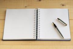 Unbelegtes Notizbuch mit silberner Feder Lizenzfreies Stockbild