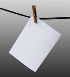 Unbelegtes Papierhängen an einem Seil Lizenzfreie Stockbilder