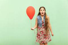 Unbelievable! The beautiful blonde teenager is sho?ked, looking at camera, with red ballon on a light green background. Stock Images