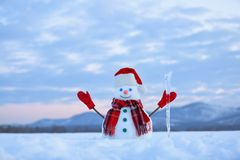 Unbelievable sunrise. Happy snowman in hat, scarf, red gloves with ice pikestaff is standing on the snow lawn. Mountains landscape. On the background stock image
