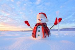 Unbelievable sunrise. Happy snowman in hat, scarf, red gloves with ice pikestaff is standing on the snow lawn. Mountains landscape. On the background royalty free stock images