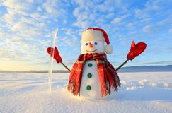 Unbelievable sunrise. Happy snowman in hat, scarf, red gloves with ice pikestaff is standing on the snow lawn. Mountains landscape. On the background royalty free stock photos