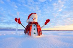 Unbelievable sunrise. Happy snowman in hat, scarf, red gloves with ice pikestaff is standing on the snow lawn. Mountains landscape on the background royalty free stock photos