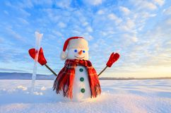 Unbelievable sunrise. Happy snowman in hat, scarf, red gloves with ice pikestaff is standing on the snow lawn. royalty free stock photos