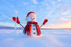 Unbelievable sunrise. Happy snowman in hat, scarf, red gloves with ice pikestaff is standing on the snow lawn. Mountains landscape on the background royalty free stock photography