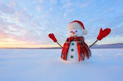 Unbelievable sunrise. Happy snowman in hat, scarf, red gloves is standing on the snow lawn. Mountains landscape on the background. Cold beautiful winter day royalty free stock images