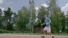 Unbelievable tennis shot. The player jumps over himself and hits the ball. The player shows his tennis skills. This session is full of many different extremely stock video footage