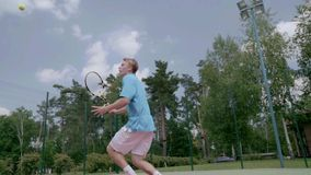 Unbelievable tennis shot. The player jumps over himself and hits the ball. The player shows his tennis skills. This session is full of many different extremely stock footage
