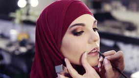 Unbelievably beautiful girl with hazelnut eyes and purple hijab on her head has unrecognizable make up artist`s hand stock video