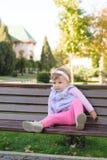 Unbequem sitzendes Mädchen Stockfoto