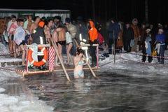 Unbestimmte Frau steigt in Wasser für Tauf ab Lizenzfreie Stockfotos