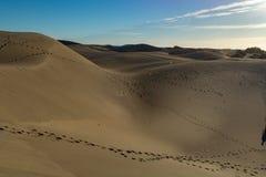 Unbestimmte Frau und Kind, die in gelbe sandige Dünen von Maspalomas, Gran Canaria, Spanien geht stockbilder