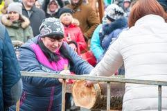 Unbestimmte Leute nehmen an der Wettbewerbsäge herauf das Logon Maslenitsa in Bryansk-Stadt teil Lizenzfreie Stockfotos