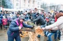 Unbestimmte Leute nehmen an der Wettbewerbsäge herauf den Klotz während Maslenitsa-Feier in Bryansk-Stadt teil Stockfotografie