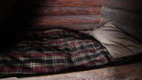 Unbewohntes verlassenes Haus der Menschen des Altertums in einer dunklen Steinhöhle mit alter Haushaltsware: Bett und Wiege stock footage