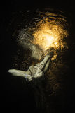Unbewusstes Mädchen lavitate Unterwasser über der Oberfläche mit Feuer Stockfotos