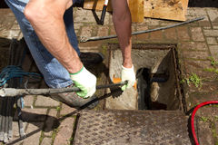 Unblocking drain. A man wearing gloves using rods to unblock a drain Stock Image