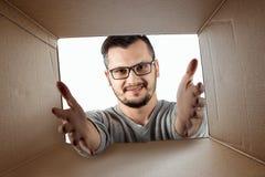 Unboxing, le fond créatif, homme joyeux ouvre la boîte et les regards dans la surprise Le paquet, la livraison, surprise, cadeau photo libre de droits