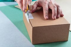 Unboxing the parcels Packed. In a cardboard box with a utility knife royalty free stock photography