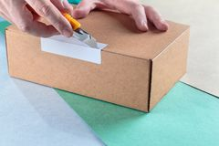 Unboxing the parcels Packed. In a cardboard box with a utility knife royalty free stock photos