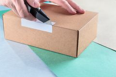 Unboxing the parcels Packed. In a cardboard box with a utility knife royalty free stock images