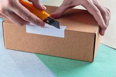 Unboxing the parcels Packed. In a cardboard box with a utility knife royalty free stock image