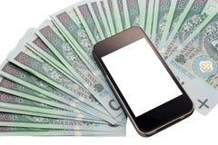 Unbranded celltelefon och raddapengar. Arkivbilder