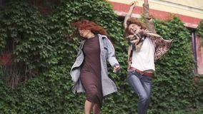 Unbridled joy of two redheaded girlfriends. girls fooling around, having fun, laughing and jumping. girlfriends having. Red-haired girlfriends are walking in the stock video footage